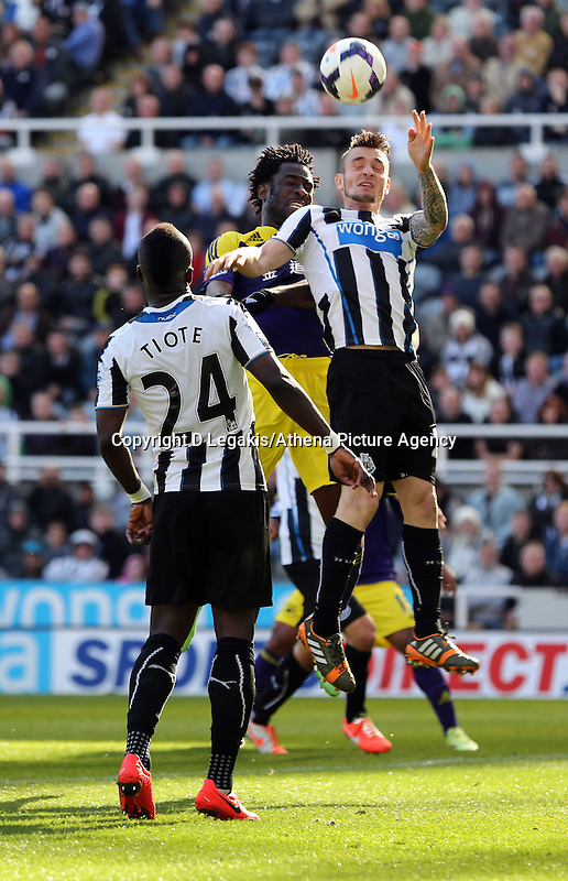Pictured: Wilfried Bony of Swansea (C) has his header stopped by a Newcastle defender. Saturday 19 April 2014<br /> Re: Barclay's Premier League, Newcastle United v Swansea City FC at St James Park, Newcastle, UK.