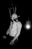 """Switzerland. Canton Valais. Bas-Valais. A bald man with blood during a chest suspension. A suspension is the act of suspending a human body from hooks that have been put through body piercings. A chest suspension, sometimes incorrectly referred to as an """"O-Kee-Pa"""", is a suspension in which the hook(s) are placed in the chest. Typically two hooks are used for this type of suspension. The suspendee's body is studied to decide the proper placement, number, and size of metal hooks which are pierced into the skin to lift the person off the ground. Depending on the position in which the body is to be suspended, multiple hooks are used. Finding the proper hook placement and number involves basic geometry and an acute understanding of human anatomy and physiology, as well as the durability of the individual's skin. If the number of hooks are too few, the suspended individual's skin will be unable to withstand the body's weight and will rip. The amount of weight that each hook supports must be distributed evenly throughout the entire body. A set of ropes are attached to the hooks in order to slowly and carefully lift an individual off the ground. 23.07.2016  © 2016 Didier Ruef"""
