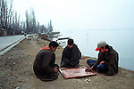 Kashmiri boys play carrom at the bank of Dal lake, Srinagar, Jammu and Kashmir
