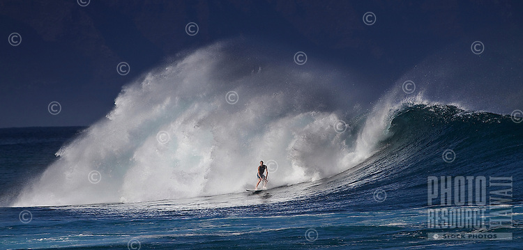 Surfer in a dramatic setting at RockPile on North Shore of Oahu.