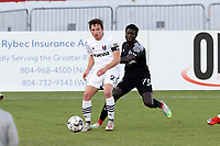 RICHMOND, VA - SEPTEMBER 30: Daniele Proch #21 of North Carolina FC plays the ball away from Cherif Dieye #70 of New York Red Bulls II during a game between North Carolina FC and New York Red Bulls II at City Stadium on September 30, 2020 in Richmond, Virginia.