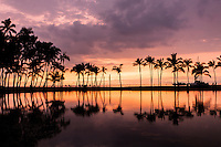A colorful sunset with palm trees reflected in the Waikoloa pond, Big Island.