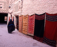 Tunisia. Tozeur. Woman walking in the Medina.