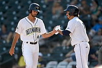 Center fielder Gene Cone (9) of the Columbia Fireflies is greeted after scoring a run in game one of a doubleheader against the Rome Braves on Saturday, August 19, 2017, at Spirit Communications Park in Columbia, South Carolina. Rome won, 8-2. (Tom Priddy/Four Seam Images)