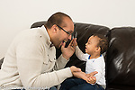 Father plays clapping peek-a-boo game with 12 month old baby boy happy interaction