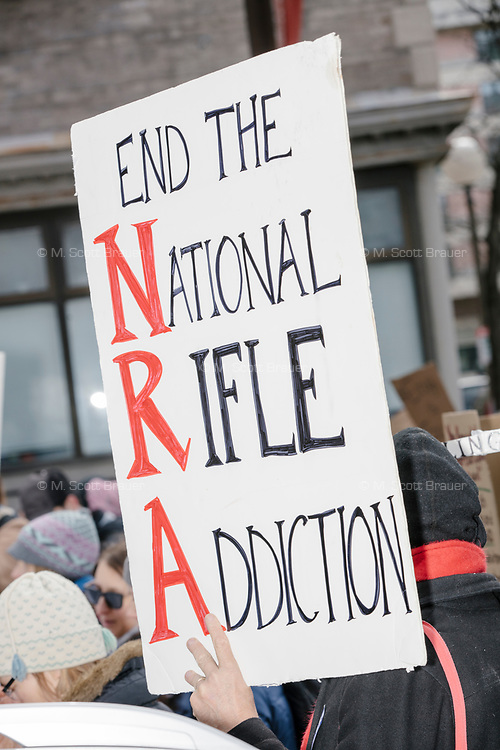 """People take part in the March For Our Lives protest, walking from Roxbury Crossing to Boston Common, in Boston, Massachusetts, USA, on Sat., March 24, 2018, in response to recent school gun violence. Here a person is holding a sign reading """"End the National Rifle Addiction."""""""