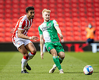5th April 2021; Bet365 Stadium, Stoke, Staffordshire, England; English Football League Championship Football, Stoke City versus Millwall; Billy Mitchell of Millwall passes through midfield under pressure from Jacob Brown of Stoke City