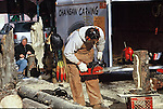 MAN AND WOMAN DISPLAY CHAINSAW CARVING TECHNIQUE ON STRETS OF GEORGETOWN