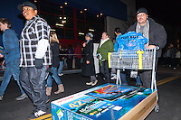 """An unknown man walks out of the Costa Mesa Best Buy on the morning of Black Friday with a cart holding a 42"""" TV and a Best Buy bag.  Behind him is a line of Occupy Orange County Irvine and Santa Ana protestors, marching in front of the store's entrance."""