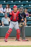 Potomac Nationals catcher Cole Leonida (13) checks the runner at first base as home plate umpire Doug Del Bello looks on during the Carolina League game against the Winston-Salem Dash at BB&T Ballpark on July 8, 2013 in Winston-Salem, North Carolina.  The Dash defeated the Nationals 12-9.  (Brian Westerholt/Four Seam Images)
