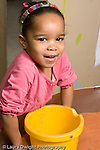 Education Preschool 3-5 year olds sand table portrait closeup of girl large yellow bucket in front of her vertical