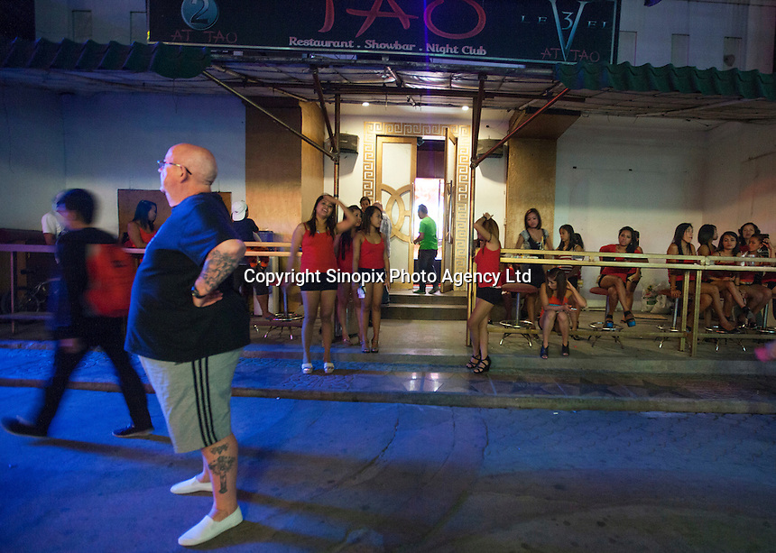 A man considers his options in front a girly bar on Fields Avenue, the main strip of bars offering cheap prostitutes that runs through Angeles City, Republic of the Philippines, 08 November 2014. The 'sin city', which sprung up on the fringes of a US Air Force base during the Vietnam war, has a reputation for cheap sex, and was a favourite destination for alleged murderer Rurik Jutting, who used to fly to Angeles City from Hong Kong for debauched weekends. The British banker is currently on remand at a secure facility in Hong Kong for allegedly murdering two Indonesian prostitutes in his flat whilst high on alcohol and cocaine.