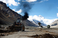 "China started building a controversial 67-mile ""paved highway fenced with undulating guardrails"" to Mount Qomolangma, known in the west as Mount Everest, to help facilitate next year's Olympic Games torch relay./// A digger belches smoke as it clears the road in front of Rongbuk Monastery  on the road to Everest Base Camp.<br /> Tibet, China<br /> July, 2007"