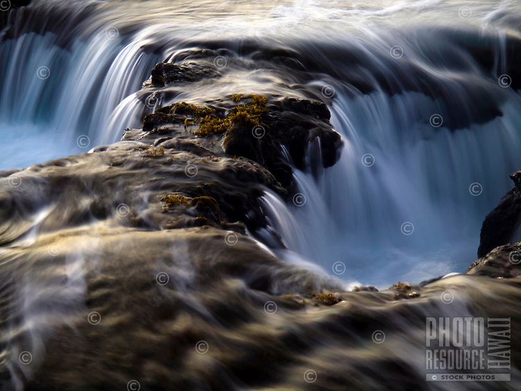 An intimate view of water rushing into a hole in the rocky shoreline at Keahole Point, Big Island.