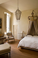 The coronet holding the bed curtains above a relatively plain double bed is carved with a fleur de lys and is combined with a Venetian chandelier in this guest bedroom