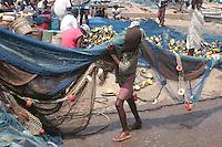 Artrisnal fishermen unloading nets from dugout pirogues. Tema, Ghana..Photograph by Peter E. Randall