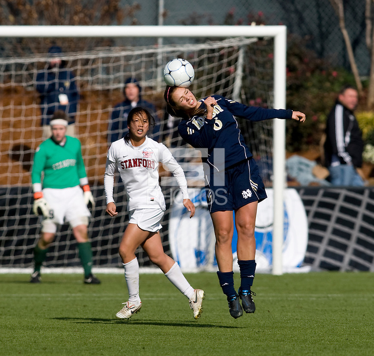 Melissa Henderson (6) of Notre Dame heads a ball in front of Rachel Quon (11) of Stanford during the final of the NCAA Women's College Cup at WakeMed Soccer Park in Cary, NC.  Notre Dame defeated Stanford, 1-0.