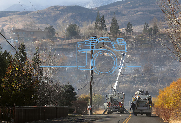 Crews work on downed power lines as a 400-acre brush fire burns in south Reno, Nev., on Friday, Nov. 18, 2011. More than 20 homes have been lost and the fire continues to burn out of control in high winds with gusts up to 60 mph. (AP Photo/Cathleen Allison)
