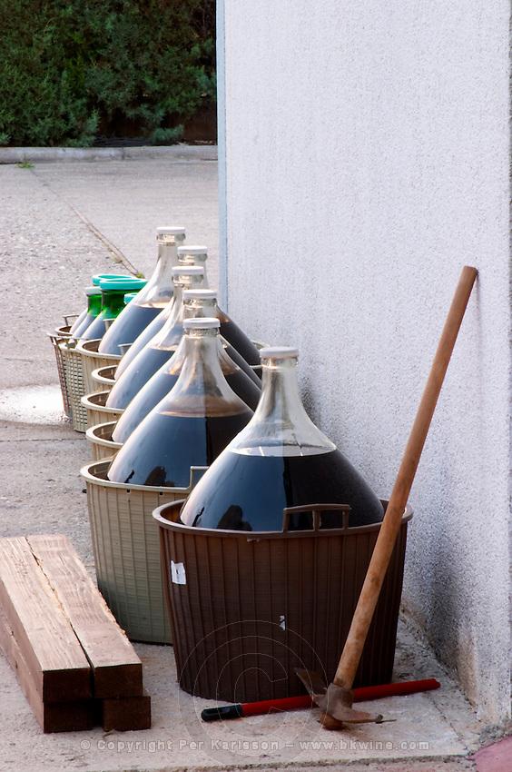 Line of demijohns with wine standing outside the winery exposed to the sun. Hercegovina Produkt winery, Citluk, near Mostar. Federation Bosne i Hercegovine. Bosnia Herzegovina, Europe.