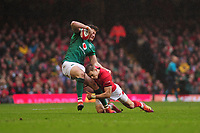 Pictured: Jacob Stockdale of Ireland is tackled by Liam Williams of Wales during the Guinness six nations match between Wales and Ireland at the Principality Stadium, Cardiff, Wales, UK.<br /> Saturday 16 March 2019