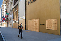 NEW YORK, NEW YORK - JUNE 08: A woman runs by  boarded up stores on June 08, 2020 in New York City. The City began first phase of reopening after nearly three months of shutdown , also Protests continue over black Americans abuse by the Police (Photo by Kena Betancur/VIEWpress via Getty Images)