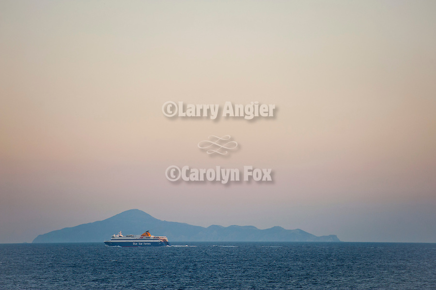 An outbound ferry boat travels to the Greek Islands at sundown on the Saronikos Kolpos Gulf in the Aegean Sea approaching the port of Piraeus, Athens, Greece
