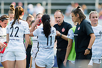 CARY, NC - SEPTEMBER 12: Portland Thorns head coach Mark Parsons talks to his players during a water break during a game between Portland Thorns FC and North Carolina Courage at WakeMed Soccer Park on September 12, 2021 in Cary, North Carolina.