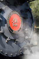 A fine art detail of a grey 1924 steam locomotive engine, Quincy No. 2 of the American Locomotive Company, with red center and name plate, and steam surrounding the front of engine,  returned to service for the first time since 1950, on the Niles Canyon Railway in northern California.
