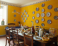 A long refectory table in this bright yellow kitchen is laid for breakfast