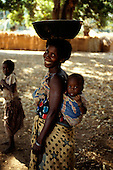 Izinga, Tanzania. Smiling woman carrying metal bowl on her head with baby in a cloth on her back.
