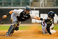 Catcher Sandy Leon #6 of the Hagerstown Suns reaches for a wide throw as Daniel Wagner #5 of the Kannapolis Intimidators slides in safely at home plate at Fieldcrest Cannon Stadium August 10, 2010, in Kannapolis, North Carolina.  Photo by Brian Westerholt / Four Seam Images