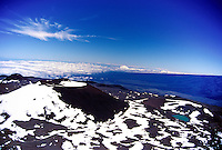 A black cindercone spotted with snow and pristine Waiau lake near the summit of Mauna Kea with high altitude clouds in the background.