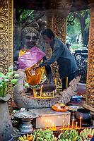 Cambodia, Siem Reap.  Worshiper Donating Money to Ya Tep, a Spirit (Neak-Ta) Who Brings Protection.