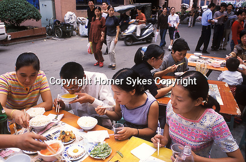 China 1990s. Yiwu Zhejiang Province out door restaurant Chinese office workers eating lunch rice chop sticks soup 1999.