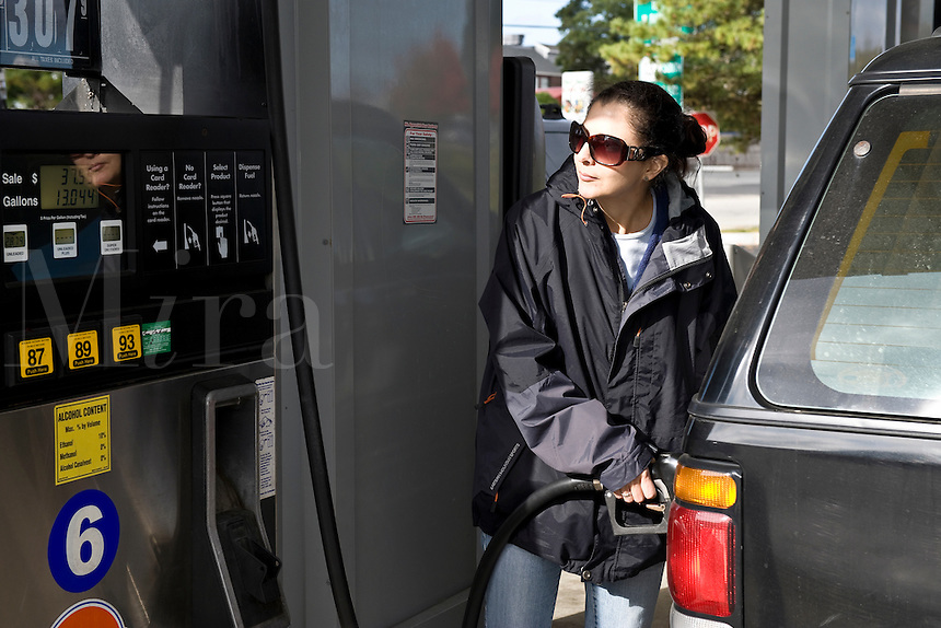 Woman filling her car at the gas pump.