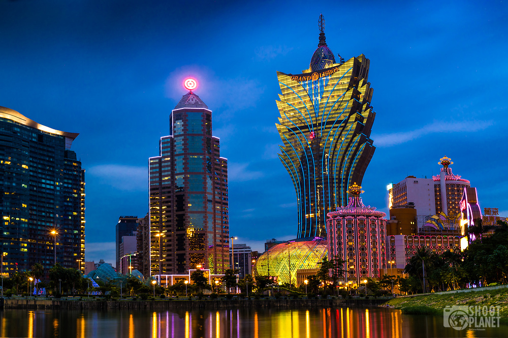 City skyline with the colorful Grand Lisboa casino lit up during twilight, with light reflections on Nam Van lake, in Macao, China