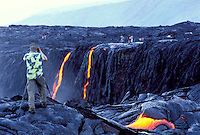 Photographer taking photos at lava flow from Kilauea, the worlds most active volcano