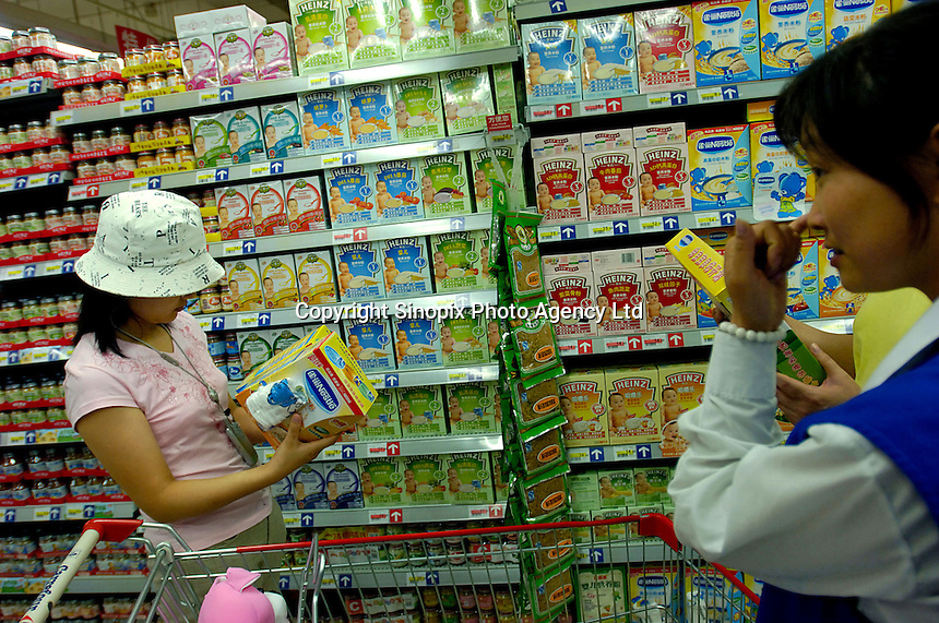 Ladies pick out and buy baby milk powder products at Heinz and Nestle shelves in a Carrefour supermarket in Beijing, China. Major international chains like Carrefour and Walmart Stores have expanded aggressively in China. Local Chinese retailers have loudly protested this and lobbied heavily for protection from the new competition in price and service that these major retailers have set off..22 Jul 2006