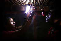 20 year old Meenakshi Diwan (left) shows villager and volunteer Ashme Wadeka how to fix the light in his house. Meenakshi is one of four women from the village of Tinginapu who has been trained in solar powered engineering by The Orissa Tribal Empowerment and Livelihoods Programme (OTELP), an organisation funded by DFID (Department for International Development) and run with the state government of Orissa. The Orissa Tribal Women's Barefoot Solar Engineers Association has now got a contract to build 3,000 solar-powered lanterns for schools and other institutions and is training other people in the community..