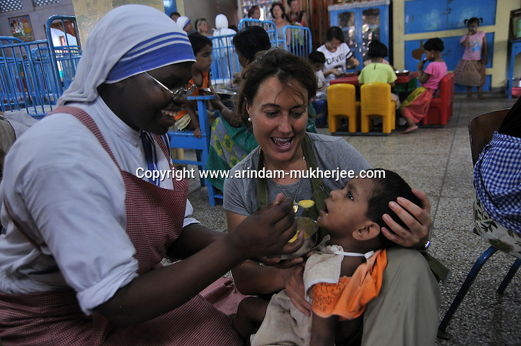 A volunteer and a nun of Missionaries of Charity trying to feed a physically chalanged child at Sishu Bhavan, which is the house for children founded by Mother Teresa.  Kolkata, West Bengal, India. 18th August 2010. Arindam Mukherjee
