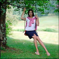 Young woman seated on tree swing.