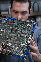 Mike Tilley inspects  the bottom of a power supply circuit board after is was soldered at AVCom Inc. in Westerville, Ohio, Thursday, Nov. 30, 2006.<br />