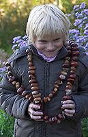 Kinder basteln mit Kastanien, Junge mit langer Kastanienkette um den Hals, Kastanie und Eichel, Eichel