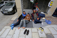 Pictured: Three migrants lie on the ground in Heyden Street, near Victoria Square Tuesday 08 March 2016<br /> Re: Migrants at Victoria Square, in central Athens, Greece.