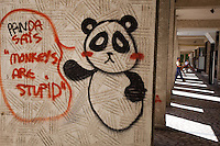 """Romania. Iași County. Iași. Graffiti on the wall: """" Panda says. Monkeys are stupid """". Amanual worker is carrying a table in his arms. Iași (also referred to as Iasi, Jassy or Iassy) is the largest city in eastern Romania and the seat of Iași County. Located in the Moldavia region, Iași has traditionally been one of the leading centres of Romanian social, cultural, academic and artistic life. The city was the capital of the Principality of Moldavia from 1564 to 1859, then of the United Principalities from 1859 to 1862, and the capital of Romania from 1916 to 1918. 8.06.15© 2015 Didier Ruef"""
