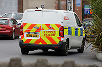 """Pictured: A police van in the car park next to the Lloyds Bank on the High Street of Gorseinon, Wales, UK. Tuesday 20 November 2018<br /> Re: Two men with machetes are being hunted by police after trying to rob a Lloyds Bank in Gorseinon, near Swansea.<br /> Armed officers, police dogs and helicopter responded to the armed robbery at 10:00am on Tuesday.<br /> According to witnesses reports, the robbers """"came through the ceiling"""" and held a member of staff by the throat.<br /> South Wales Police said nobody was hurt during the incident.<br /> A witness said: """"They had a girl from Lloyds by the throat. After robbing the bank they used a car to drive off."""""""