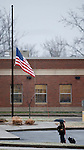 TORRINGTON, CT 17 DECEMBER- 121712JS03- A woman makes her way into Torringford School in Torrington past the American flag flying at half-staff on Monday as teachers and local children return to school following the deadly shooting in Newtown on Friday. Jim Shannon Republican American