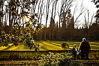 Prince's garden in Aranjuez, the beautiful garden of the royal court with old trees, gorgeous houses, mansions, wild animals and near the Tajo river. Two elderly persons taking a rest