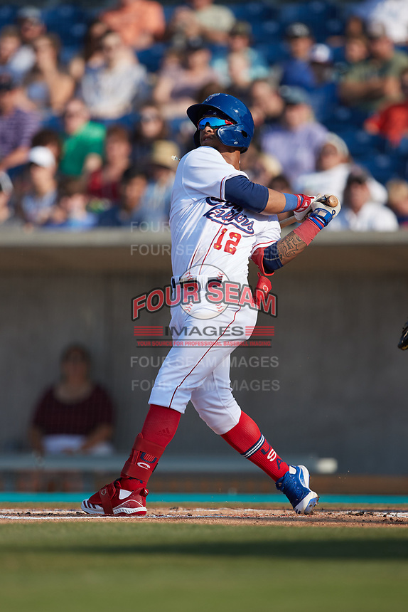 Jose Rodriguez (12) of the Kannapolis Cannon Ballers follows through on his swing against the Charleston RiverDogs at Atrium Health Ballpark on July 4, 2021 in Kannapolis, North Carolina. (Brian Westerholt/Four Seam Images)