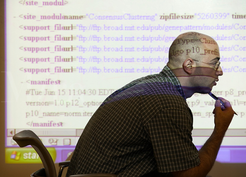 Man profiled in front of projection of HTML coding at the Broad Institute. This is a research collaboration of MIT, Harvard University and affiliated hospitals, and the Whitehead Institute for Biomedical Research (genomics, genetics, DNA). Cambridge, Mass